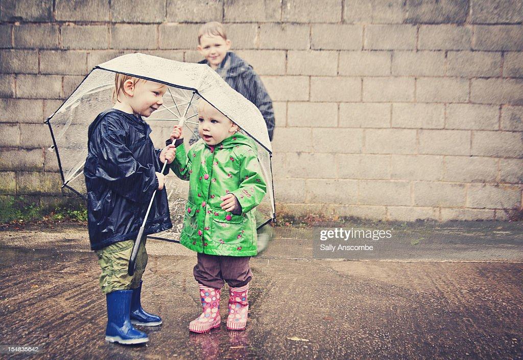 Two children sharing an umbrella in the rain : Stock-Foto