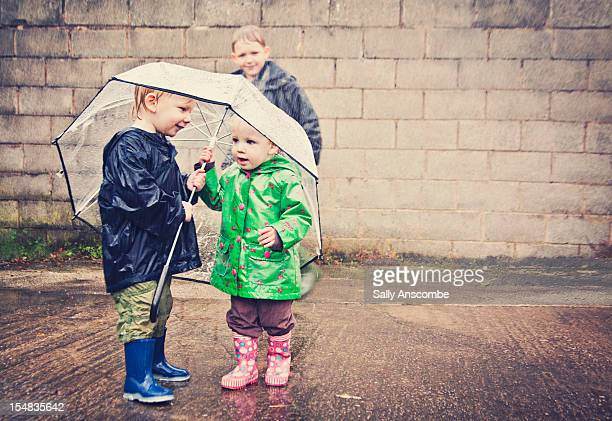 Two children sharing an umbrella in the rain