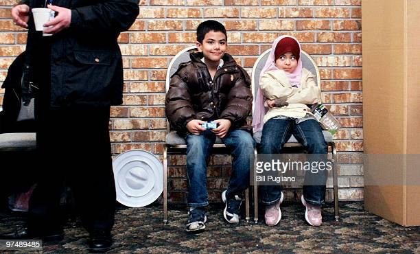 Two children sit and wait as Iraqi expatriates casts their ballots during voting for the Iraqi parliamentary election at a polling station March 6,...