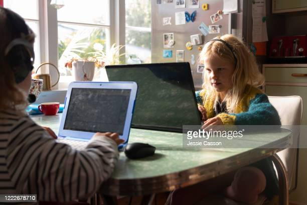 two children sit at a table studying on their laptops - ホームスクーリング ストックフォトと画像