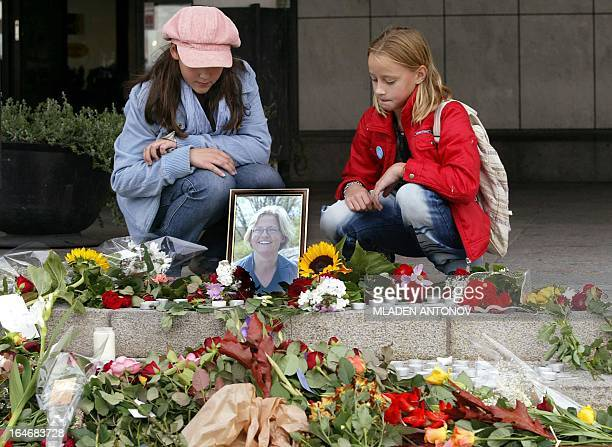 Two children sit next to a portrait of slain Swedish foreign Minister Anna Lindh at the entrance of the City Hall on the central square of her birth...
