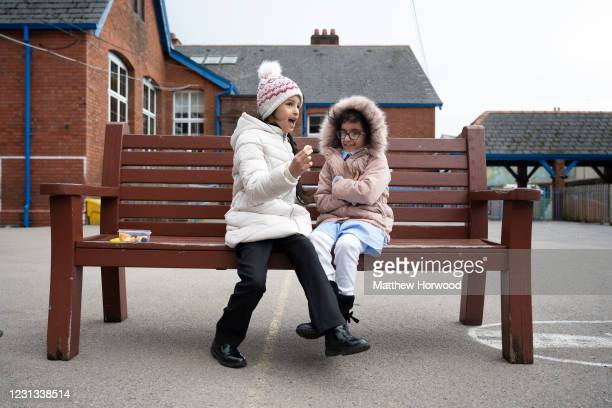 Two children sit on a bench during a lunch break at Roath Park Primary School on February 23, 2021 in Cardiff, Wales. Children aged three to seven...