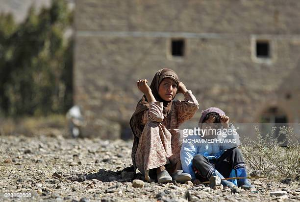Two children sit outside the rubble of a house hit by Saudiled coalition air strikes two days earlier on the outskirts of the Yemeni capital Sanaa on...