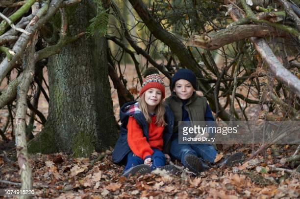 Two children sitting in their den in Autumnal woodland