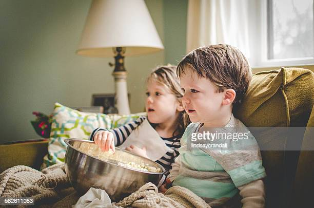 Two children sitting on the sofa watching TV and eating popcorn
