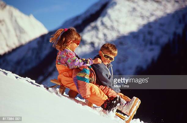 two children (5-7) sledging down mountain slope - ski pants stock pictures, royalty-free photos & images