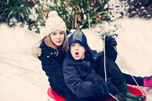 Two children sledging in the snow - gettyimageskorea