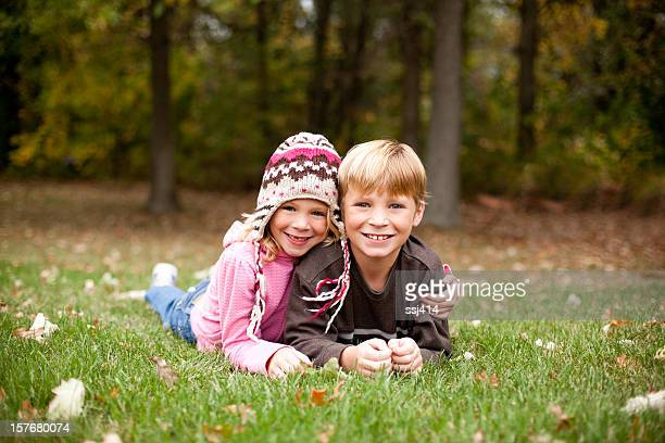 Two Children Smiling for Camera While Outdoors
