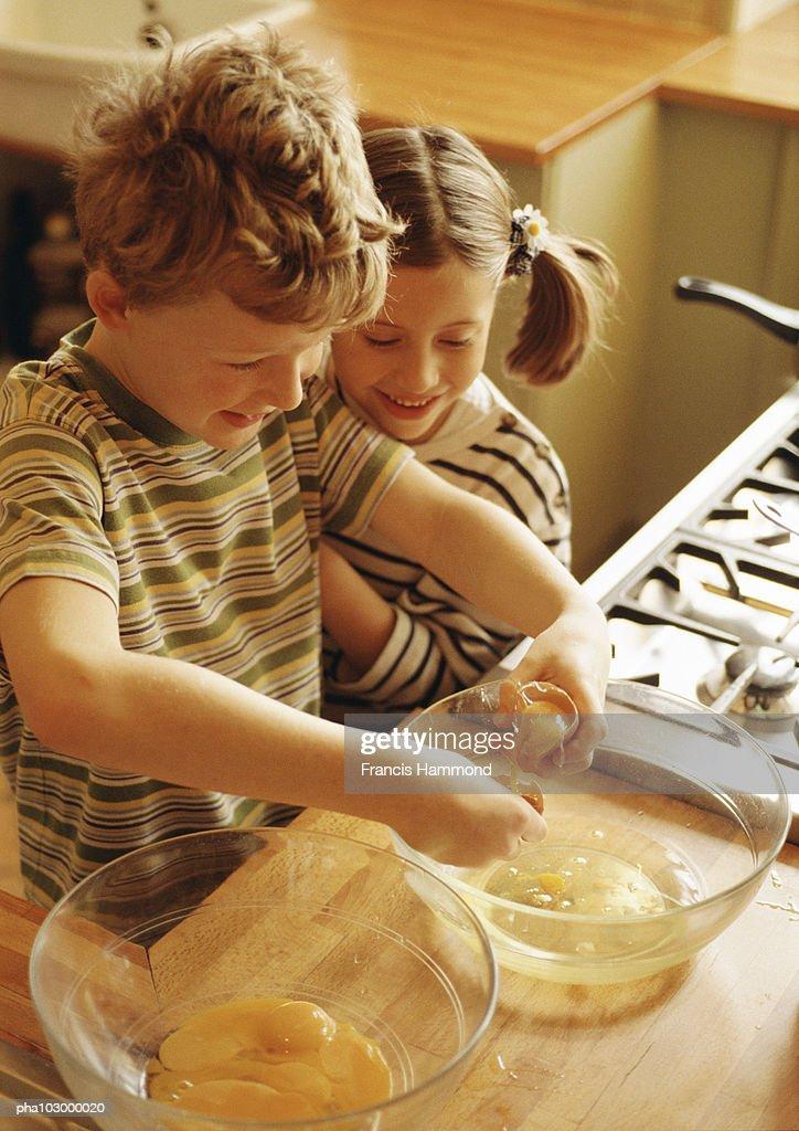Two children smiling, one beating up egg whites : Stockfoto
