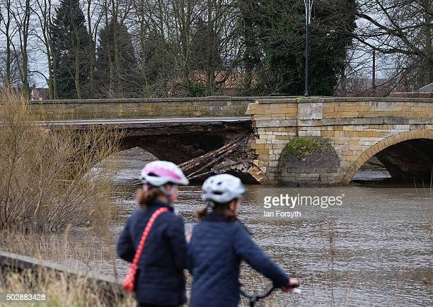 Two children stand and look at the bridge over the River Wharfe which collapsed due to heavy flooding on December 30 2015 in Tadcaster England Heavy...