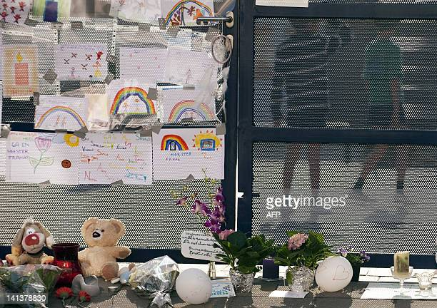 Two children stand behind a tribute for the victims at the entrance of the primary school SintLambertusschool in Heverlee on March 15 2012 Classmates...