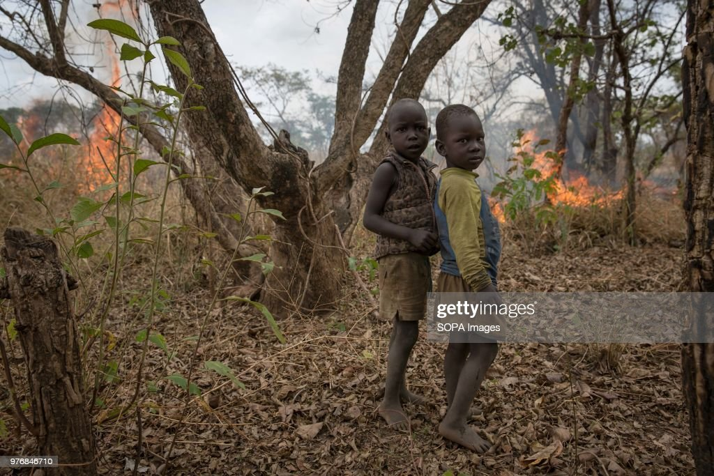 Two children stand in front of a fire their father lit to... : News Photo