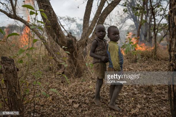 Two children stand in front of a fire their father lit to clear land for farming Medics create prosthetics for some of the thousands of Ugandan land...