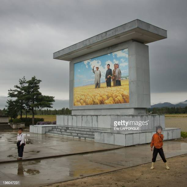 Two children stand in front of a poster with Kim Jong Il and farmers on September 15 2011 in Hamhung Hamgyong Province North Korea