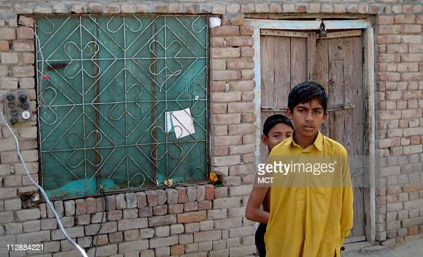 Two children stand in front of the family home of Ajmal Ameer Kasab in Faridkot Pakistan
