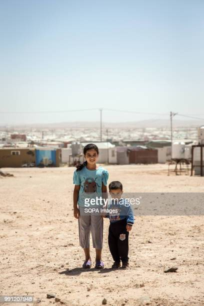 Two children stand in front of Zaatari refugee camp There are about 14 million Syrian refugees in Jordan and only 20 percent are living in the...