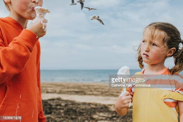 two children stand on a beach by an ocean holding melting vanilla ice-creams - china: through the looking glass bildbanksfoton och bilder