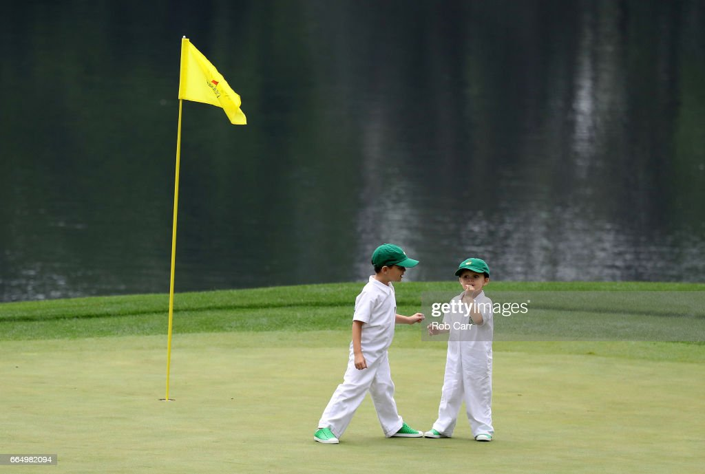 Two children stand on a green during the Par 3 Contest prior to the start of the 2017 Masters Tournament at Augusta National Golf Club on April 5, 2017 in Augusta, Georgia. The Par 3 Contest was later cancelled due to inclement weather.