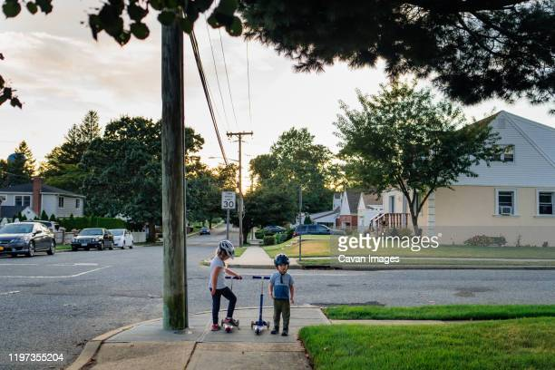 two children stand on a street corner with their scooters. - american suburb neighborhood stock-fotos und bilder
