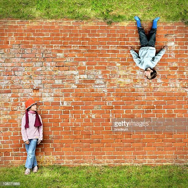 Deux enfants debout contre le mur de briques