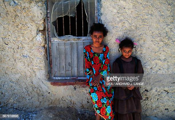 Two children standing near a window Mirbat Oman