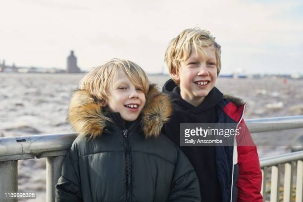 two children stood by the river mersey - sally anscombe stock pictures, royalty-free photos & images