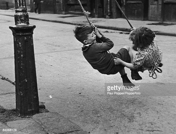 Two children swinging from a lamppost in a Dublin street during a teachers' strike at their school 6th November 1946