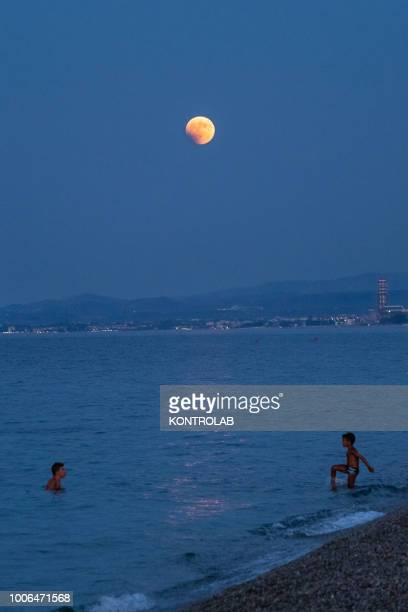 Two children take a bath during the total eclipse of the moon which turns red on the Ionian sea The lunar eclipse is considered the longest eclipse...