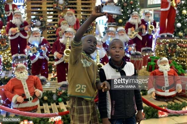 Two children take a selfie picture with a cellphone in front a podium full of Santa Claus dolls on December 22 2016 at the Thika Road Mall in Nairobi...