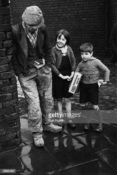 Two children talking to an unemployed man on a street corner in Wigan Original Publication Picture Post 228 Wigan pub 1939