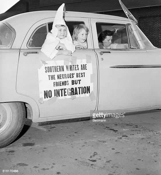 Two children the boy wearing a white hood watch a Ku Klux Klan cross burning from a car which is fixed with a sign protesting integration