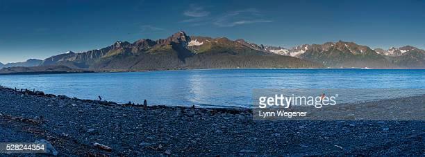 two children throw rocks into resurrection bay at seward alaska, southcentral, summer. usa. panorama. - golfo do alasca imagens e fotografias de stock