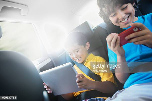 Two children travelling in the back seat of a car, one using a digital tablet and one a handheld game.