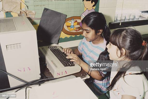 Two children using a computer in school USA May 1984