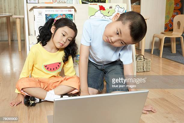 Two children using a laptop computer in the classroom.