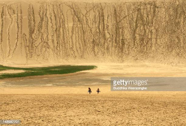 Two children walk on Tottori sand dunes on July 21 2012 in Tottori Japan The dunes are over 30 km² but are decreasing in size as a result of the...
