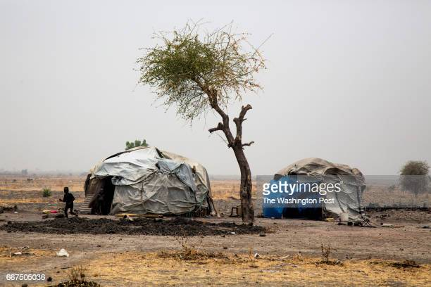 Two children walk out from their shelter in Dablual , South Sudan, on March 23, 2017. Hundreds of people have recently fled Dablual, still under...