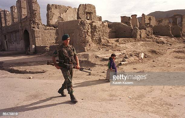 Two children walk through a devastated area of Kabul Afghanistan whilst an ISAF soldier patrols the neighborhood on the first spring after the...