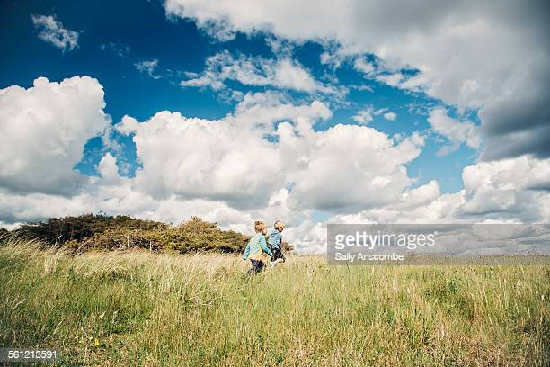 two children walking in a field - only boys stock photos and pictures