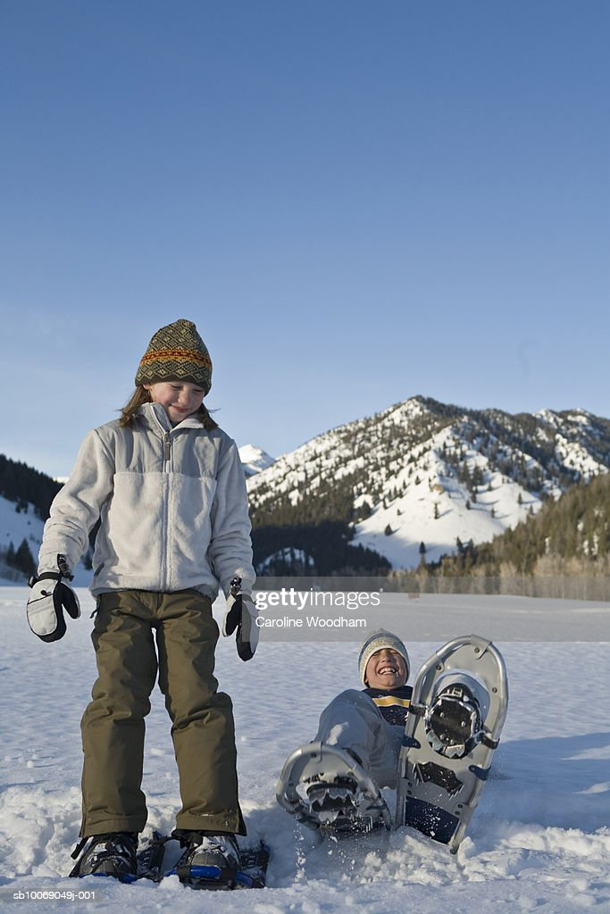 Two children (9-10) walking in snowshoes in mountains, laughing : Stockfoto