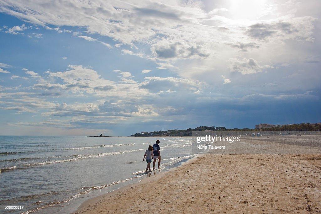 Two children walking on the beach : Stock Photo