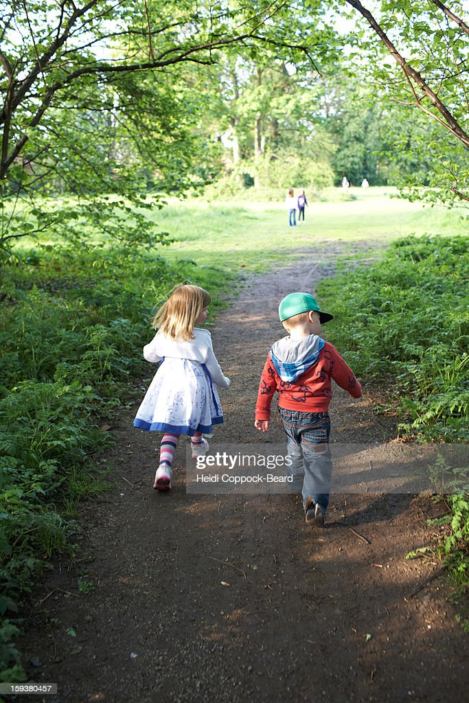 Two children walking through forest : Stock Photo