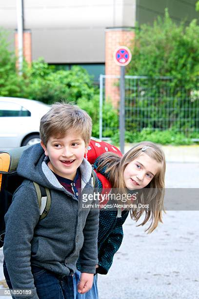 Two children walking to school, keeping an eye on the traffic, Munich, Bavaria, Germany