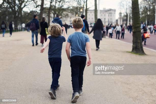 two children walking together - ロンドン ザ・マル ストックフォトと画像