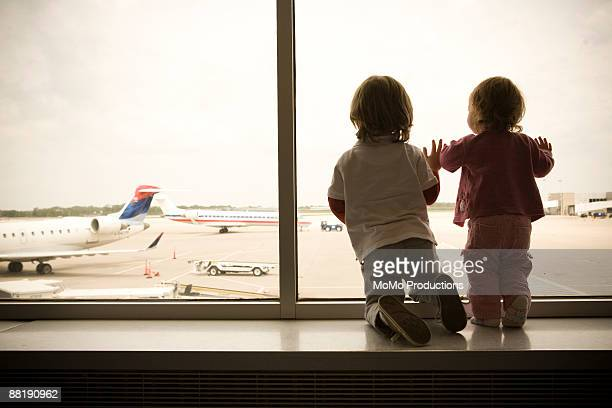 two children watch planes land - kid in airport stock pictures, royalty-free photos & images