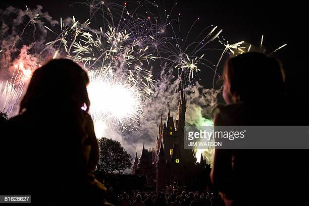 Two children watch the fireworks display as it explodes over Cinderella's Castle at Disney World's Magic Kingdom in Orlando, Florida, May 7, 2008....