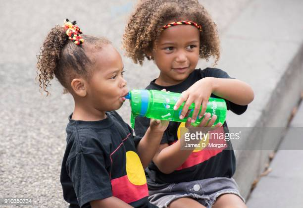 Two children wearing aboriginal flag tshirts join protestors as they gather at State Parliament on January 26 2018 in Melbourne Australia Australia...