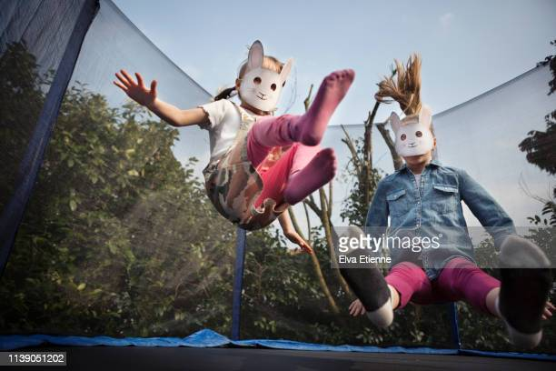 two children wearing rabbit masks and bouncing on a trampoline - easter family - fotografias e filmes do acervo