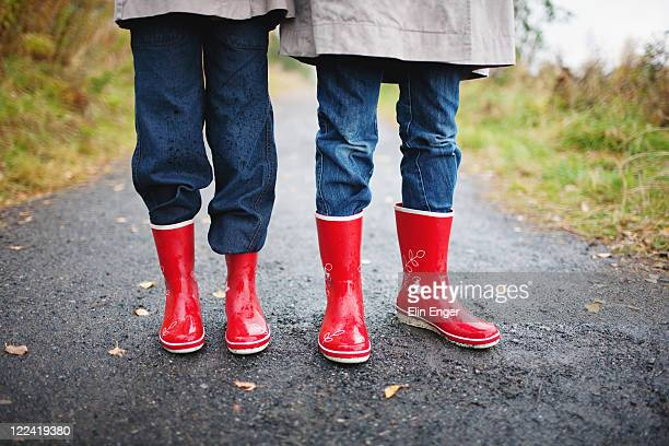 Two children wearing red rubber boots