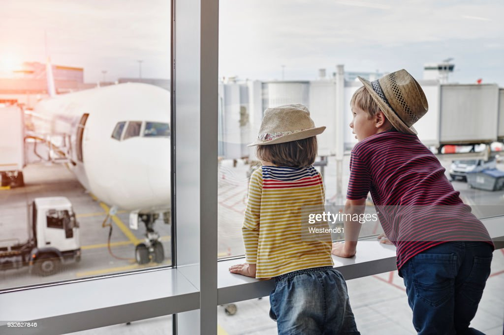 Two children wearing straw hats looking through window to airplane on the apron : Stock Photo